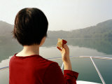Woman Eats an Apple While Riding in a Boat in Sun Moon Lake, Taiwan Photographic Print by  xPacifica