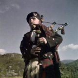 Bagpiper in Cameron Tartan Plays a Lament Photographic Print by B. Anthony Stewart
