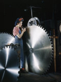 Factory Worker Inspects Notches of a Large Steel Saw Blade Photographic Print by Willard Culver