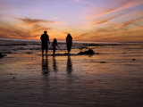 Rear View of a Family with One Child Walking on a Beach at Sunset Photographic Print by James Forte