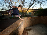 Jack Belle, a Traceur Vaulting a Wall Using Parkour in Urban Jungle Photographie par Brooke Whatnall