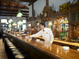 Bartender Wipes the Bar Counter in Raffles Hotel, Singapore Fotografisk tryk af  xPacifica