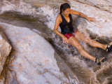Kim Havell Floats Down a Natural Water Slide in a Canyon Photographic Print by Pete McBride