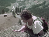 Woman Crawls to the Edge of a Cliff to Pick Edelweiss Flowers Photographic Print by W. Robert Moore