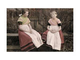 Two Schoolgirls Sit on a Bench, Dressed in Hand-Embroidered Dresses Photographic Print by Wilhelm Tobien