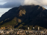 Town at the Base of a Large Cloud-Shrouded Mountain Photographic Print by Mattias Klum