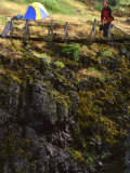 Backpacker Exploring a Suspension Bridge by His Tent Photographic Print by Kate Thompson