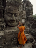 Young Buddhist Monk Prays at a Relief Statue of Buddha Fotografisk tryk af Paul Chesley