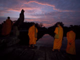 Buddhist Monks Leave the Angkor Wat Temple Complex at Sunset Fotografisk tryk af Paul Chesley
