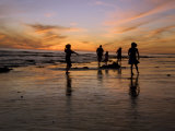 Children Playing on the Beach at Sunset with Family in the Background Photographie par James Forte