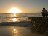 Man Watches the Sunset at Waikiki Beach in Honolulu, Hawaii Photographic Print by Charles Kogod