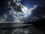 Backlit Clouds Reflections in Water Photographic Print by Raul Touzon