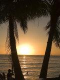 Sun Sets in Pacific Ocean at Waikiki Beach, Honolulu, Hawaii Fotografisk tryk af Charles Kogod