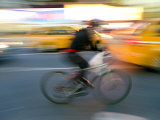 Bicyclist Sweeps Past Taxicabs in Times Square Photographic Print by Scott Warren