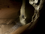A caver moves through a wet passage in McBride's Cave. Photographic Print by Stephen Alvarez