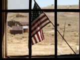 American Flag Is Displayed in the Window of an Abandoned Building Photographic Print by Charles Kogod