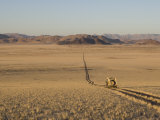 Land Rover on a One Lane Roadway Through a Dry Desert Landscape Photographic Print by Michael Polzia