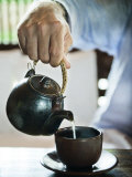Masculine Hand Pouring Tea into a Cup Photographic Print by  xPacifica