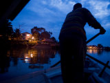 Boatman Paddling over to the North Side of the Sarawak River Photographic Print by Mattias Klum