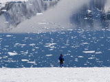 Man at a Calm Bay with Pieces of Pack Ice and Mountain Reflions Photographic Print by John Dunn