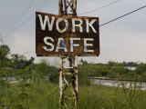 Rusty Sign under Powerlines Warns People to Work Safely Photographic Print by Tyrone Turner