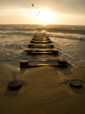 Atlantic Ocean Waves Break Against Pilings at Sunrise Photographic Print by Stephen St. John