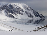 Three Skiers Descend Toward a Mainly Ice Free Bay Bounded by Mountains Photographic Print by John Dunn
