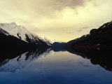 Mountains Reflected on a Still Lake Photographic Print by Nick Norman