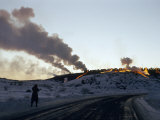 Silhouetted Figure Walks Road Below Hillside Where Molten Slag Flows Photographic Print by B. Anthony Stewart