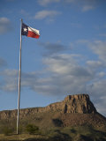 Texas Flag and Rugged Landscape in the Distance Photographic Print by Richard Nowitz