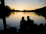 Couple Sit on a Bench in Front of a Lake at Sunset Photographic Print by Hannele Lahti