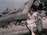 Girl Sits on a Log Among Cigar Boxes Crafted from Cedar Trees Photographic Print by Clifton R. Adams
