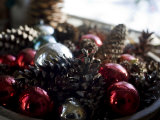 Bowl of Christmas Balls and Pine Cones Sit in a Window Photographic Print by Hannele Lahti