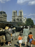 Mother Hurries Children Past Book Stalls Near Notre Dame De Paris Lámina fotográfica por Justin Locke