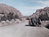 Group Stands Beside a Car on a Highway Through the Desert Photographic Print by Clifton R. Adams