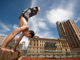 Male Gymnast Does a Handstand on the Edge of Wall in Cityscape Reproduction photographique par Brooke Whatnall