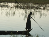 Woman Stands at the End of a Rowboat with a Fishing Spear Photographic Print by Lynn Abercrombie