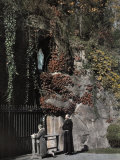 Two People Stand in Front of a Replica of the Grotto of Lourdes Photographic Print by Charles Martin