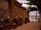 Motorcycles Along a Wall at the Waterfront at Sunset on Koh Lanta Photographic Print by Rebecca Hale