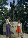 Mother and Daughter Holding Hands Stand Beside Statue of Sacagawea Photographic Print by Ralph Gray