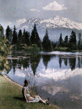 Girl Sits by a Lake with Snow-Capped Mountains in the Background Photographic Print by Charles Martin