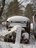 Rusted Antique School Bus Sits in the Woods Covered in Fresh Snow Photographic Print by Hannele Lahti