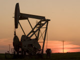 Oil Drilling Pump Silhouetted Against the Sunset in North Dakota Photographic Print by Phil Schermeister