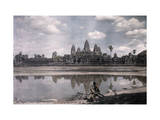 Person Sits by a Moat Which Surrounds the Towers of Angkor Vat Photographic Print by Gervais Courtellemont