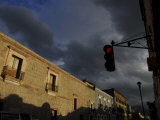 Red Traffic Light and Sunlit Buildings under a Moody Sky Photographic Print by Raul Touzon