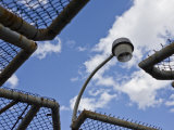 Lamppost Looms over Wrought Iron Fencing under a Blue Sky Photographic Print by Hannele Lahti