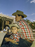 Father and Son Wearing Matching Shirts and Jeans Sit Side by Side Lámina fotográfica por Justin Locke