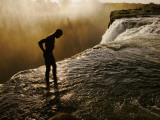 Swimmer Stands at the Lip of a Hidden Pool at Victoria Falls Fotografisk tryk af Annie Griffiths Belt