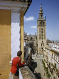 Woman Stands on Terrace Overlooking Street Leading to the Giralda Photographic Print by Luis Marden