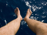 Looking Down at the Water Below a Pair of Men's Legs and Feet Photographic Print by Mattias Klum